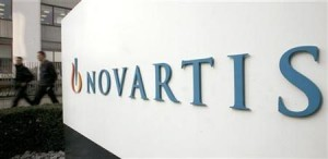 People walk past the logo of Swiss drugmaker Novartis at the company's plant in Basel