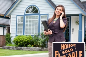 real-estate-agent-in-front-of-sold-home